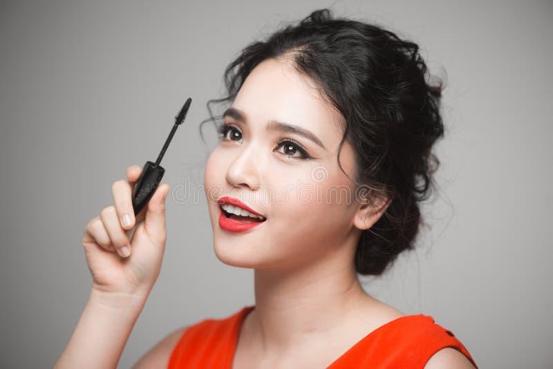Härlig ung asiatisk kvinna som gör makeup genom att använda mascara på henne som är ey royaltyfri bild