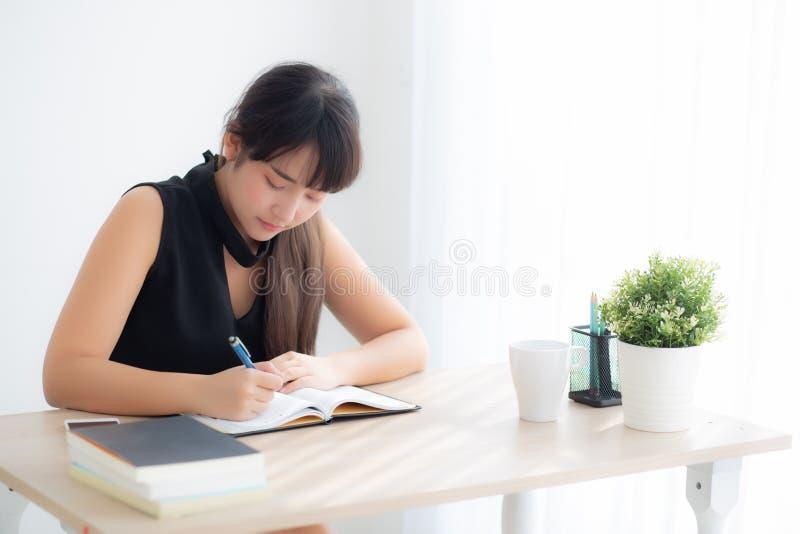 Härlig ung asiatisk kvinna som ler den sittande studien och lär skriva anteckningsboken och dagboken i vardagsrummet hemma arkivfoto