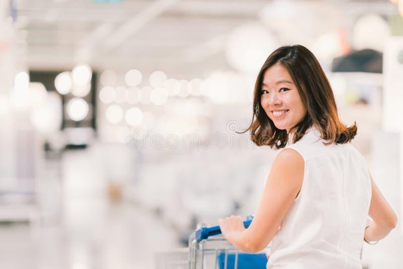 Härlig ung asiatisk kvinna som ler, med shoppingvagnen, köpcentret eller varuhusplatsen, suddighetsbokehbakgrund arkivbilder