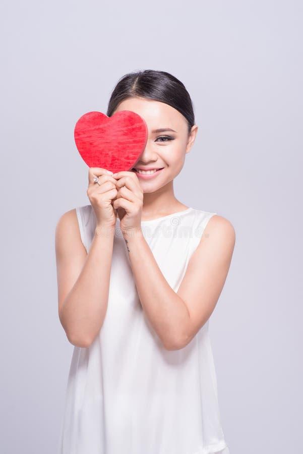 Härlig ung asiatisk kvinna som rymmer röd hjärta på vit royaltyfria bilder