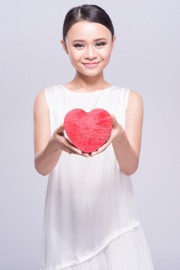 Härlig ung asiatisk kvinna som rymmer röd hjärta på vit arkivfoton