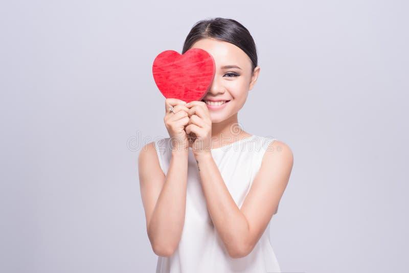 Härlig ung asiatisk kvinna som rymmer röd hjärta på vit royaltyfria foton