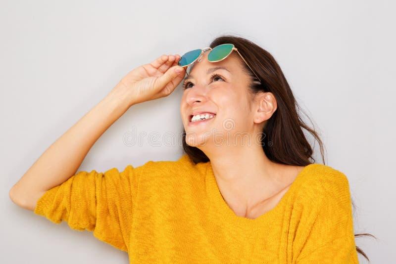 Härlig ung asiatisk kvinna som skrattar med solglasögon mot grå bakgrund royaltyfri foto
