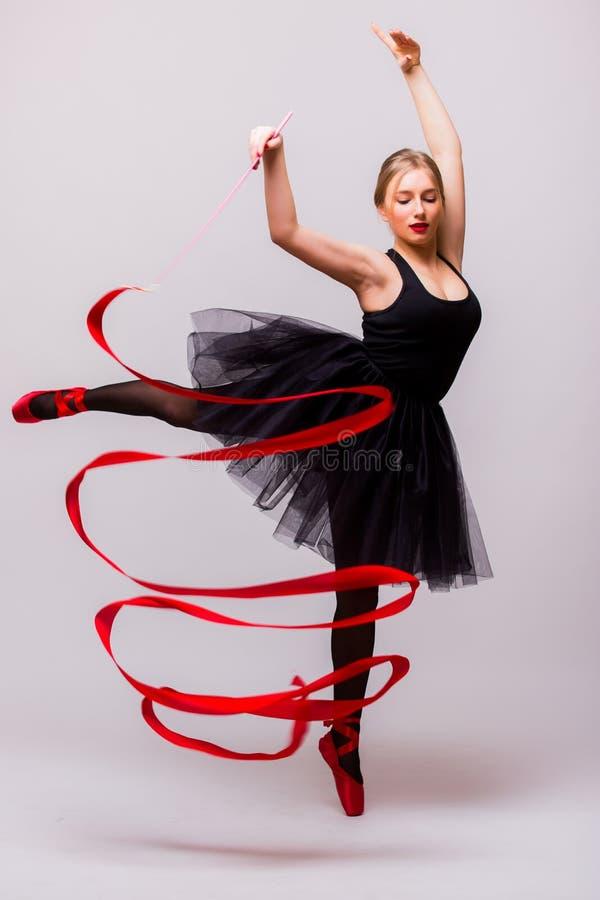 Härlig ung blond övning för calilisthenics för utbildning för kvinnabalettgymnast med det röda bandet med röda skor royaltyfri bild