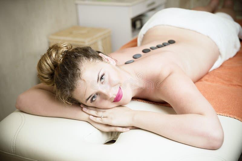 Härlig ung blond caucasian kvinna som får en varm stenmassage i brunnsortmitt arkivfoton