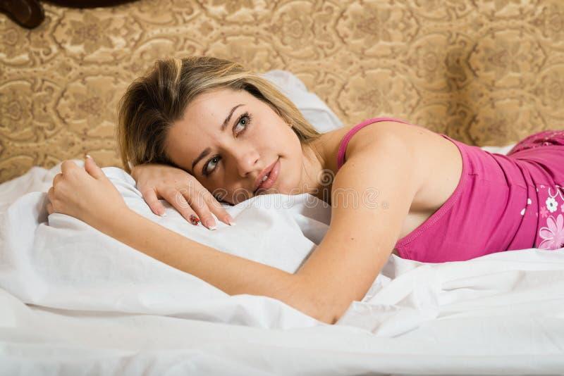 Härlig ung blond dam i sängen hemma som kopplar av royaltyfri foto