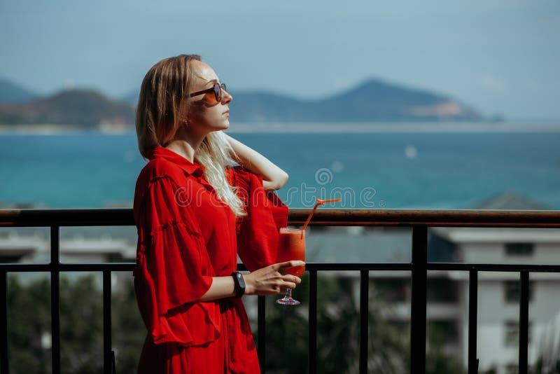 Härlig ung blond flicka i röd klänning och solglasögon som dricker den röda coctailen från ett exponeringsglas på balkong Mot royaltyfri fotografi