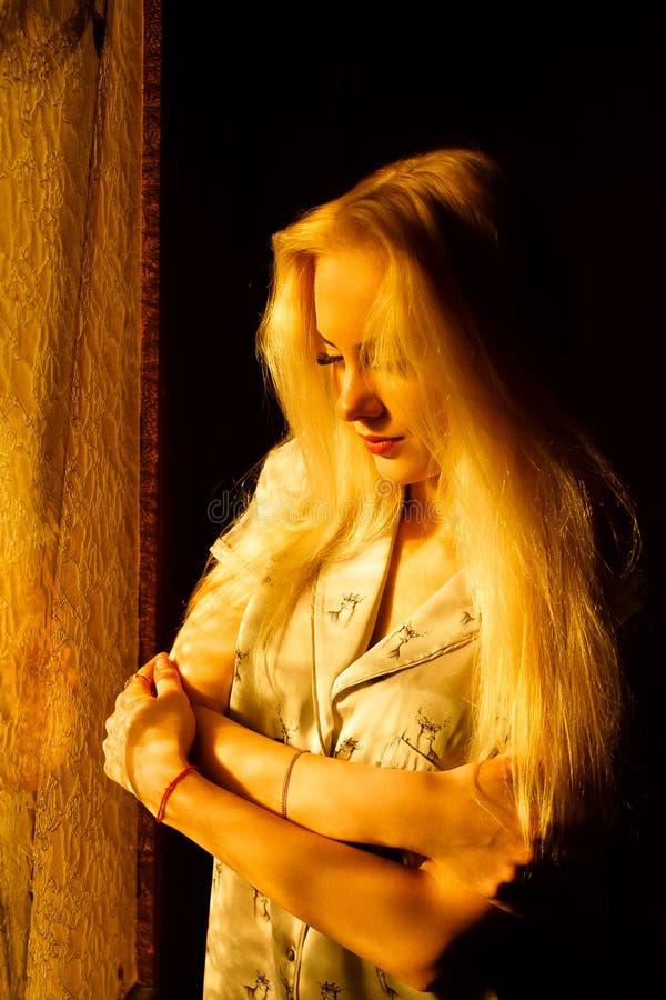 Härlig ung blond flicka med en nätt framsida och härliga ögon Dramatisk stående av en kvinna i mörkret Drömlik kvinnlig blick arkivbilder