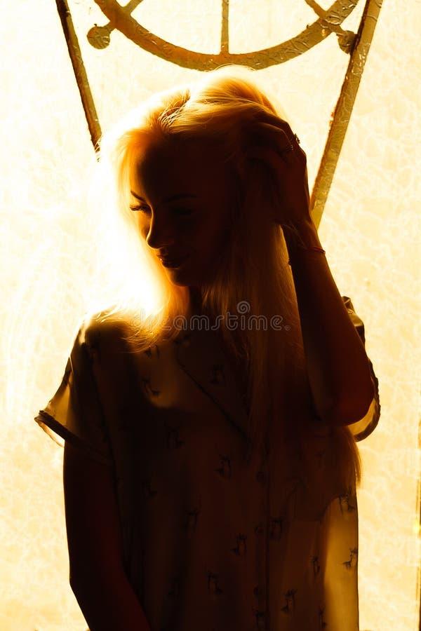 Härlig ung blond flicka med en nätt framsida och härliga ögon Dramatisk stående av en kvinna i mörkret Drömlik kvinnlig blick fotografering för bildbyråer