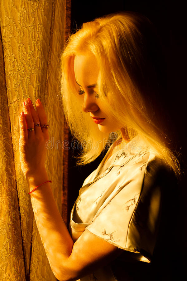 Härlig ung blond flicka med en nätt framsida och härliga ögon Dramatisk stående av en kvinna i mörkret Drömlik kvinnlig blick arkivfoto