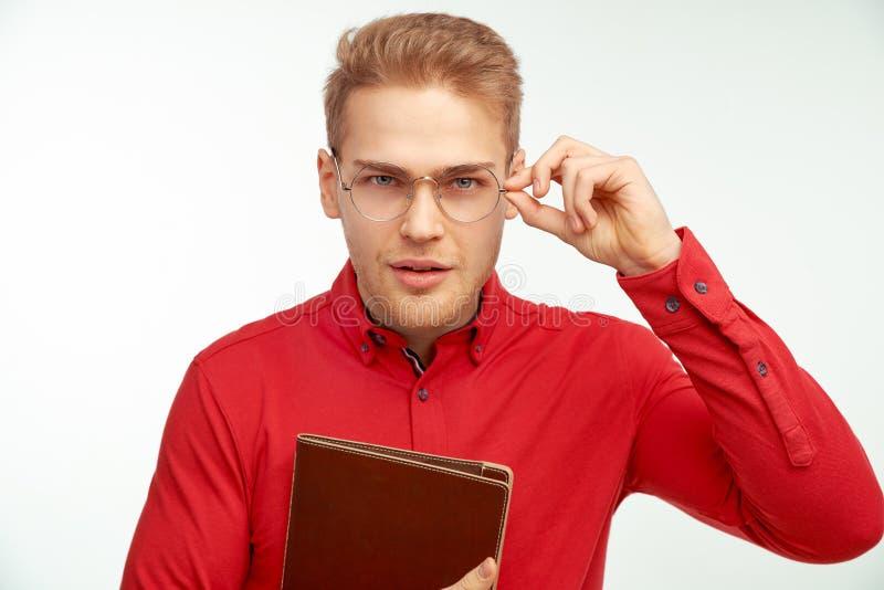 Härlig ung blond grabb som rymmer exponeringsglas och skelar att försöka att läsa inskriften framme av honom royaltyfria bilder