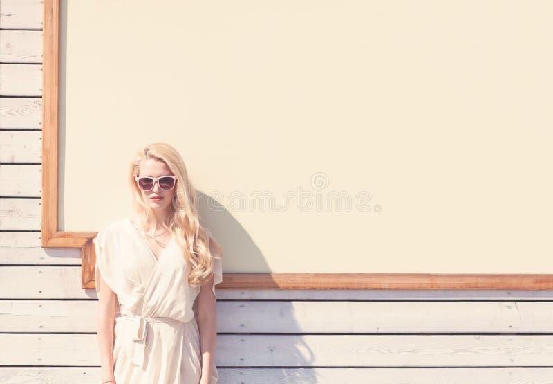 Härlig ung blond kvinna för utomhus- sinnlig modestående för sommar av en vit klänning i solglasögon på gatan på bakgrunden arkivbild