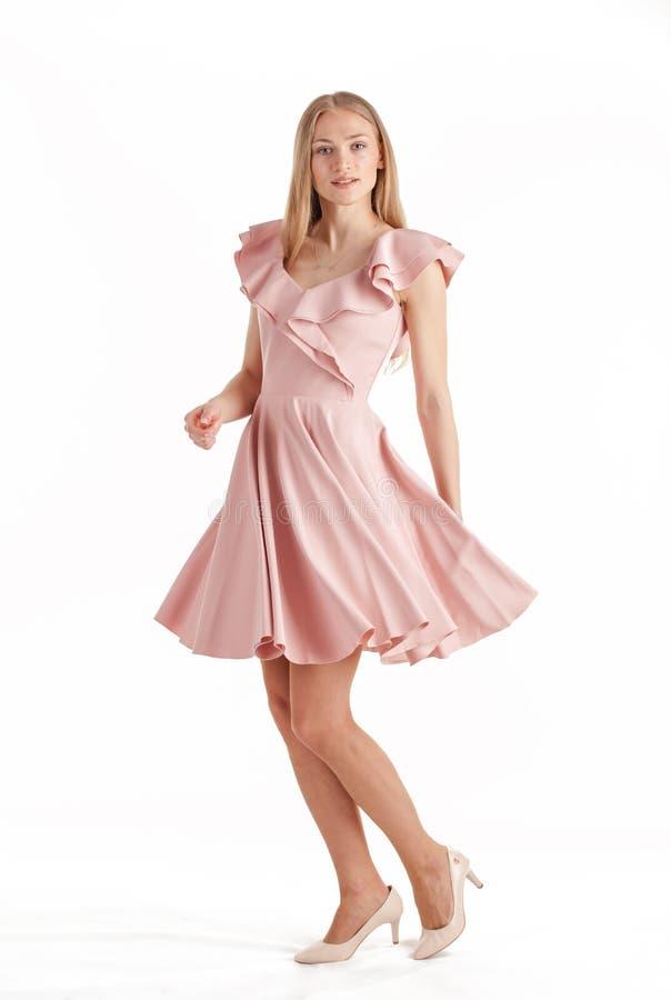 H?rlig ung blond kvinna i den rosa kl?nningen som isoleras p? vit bakgrund royaltyfri fotografi