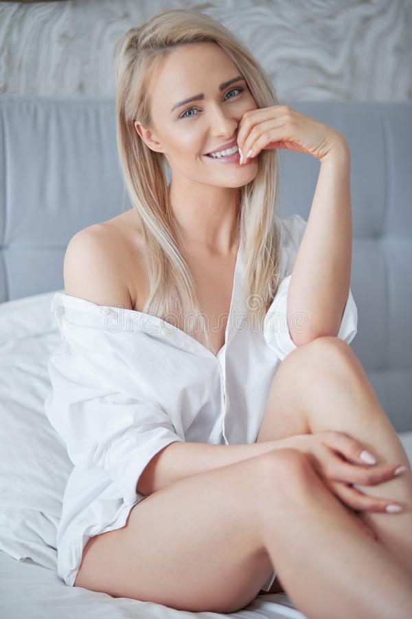 Härlig ung blond kvinna i den vita skjortan som ler på kameran royaltyfria foton