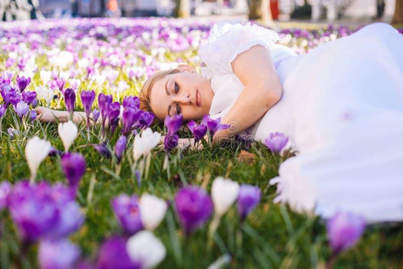 Härlig ung blond kvinna med den blåa vit klänningen för ögon som och ligger på mattan bland vårblommakrokusarna royaltyfria foton