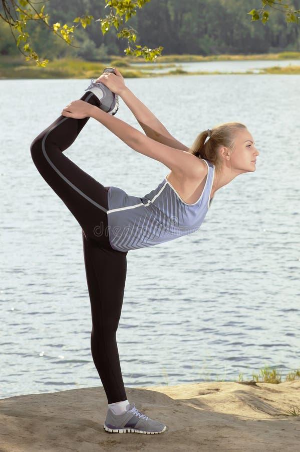 Härlig ung blond kvinna med den idrotts- kroppen som gör sträcka övning utomhus royaltyfria foton