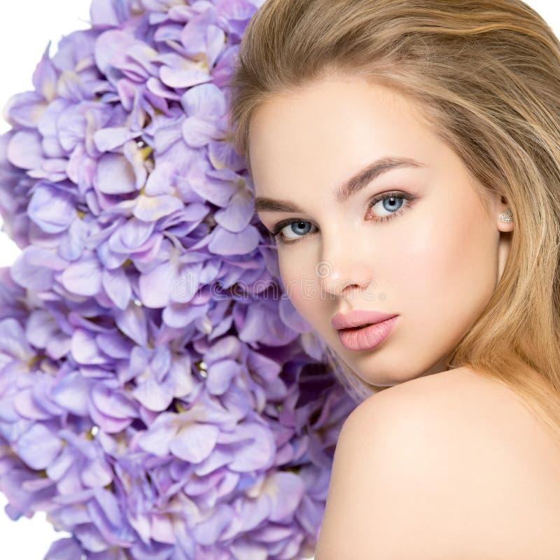 Härlig ung blond kvinna med den near framsidan för blommor royaltyfri fotografi