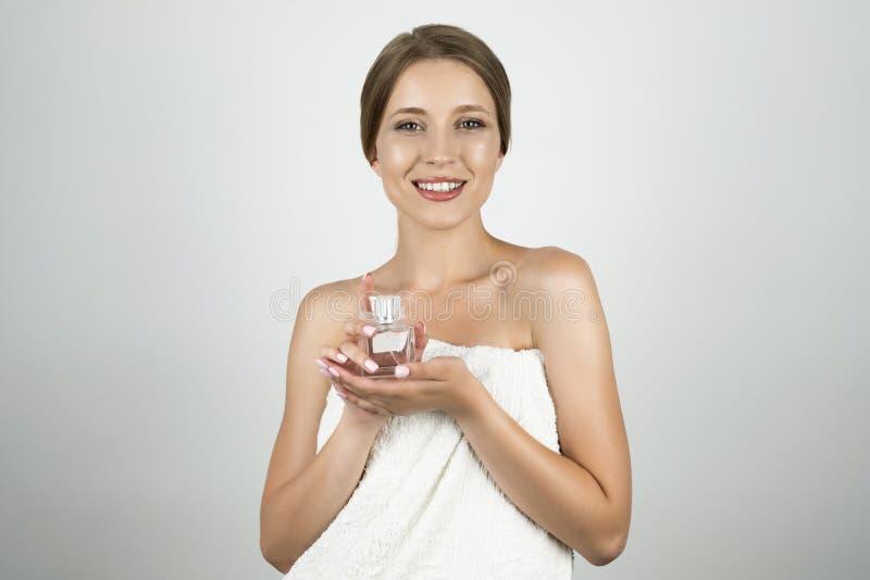 Härlig ung blond kvinna med den vita handduken över hennes kropp som rymmer parfume isolted vit bakgrund arkivfoto