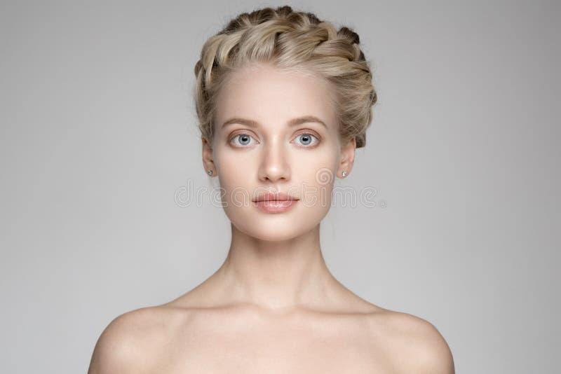 Härlig ung blond kvinna med flätad trådkronahår arkivfoto