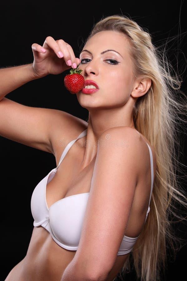 Härlig ung blond kvinna med jordgubben arkivfoto