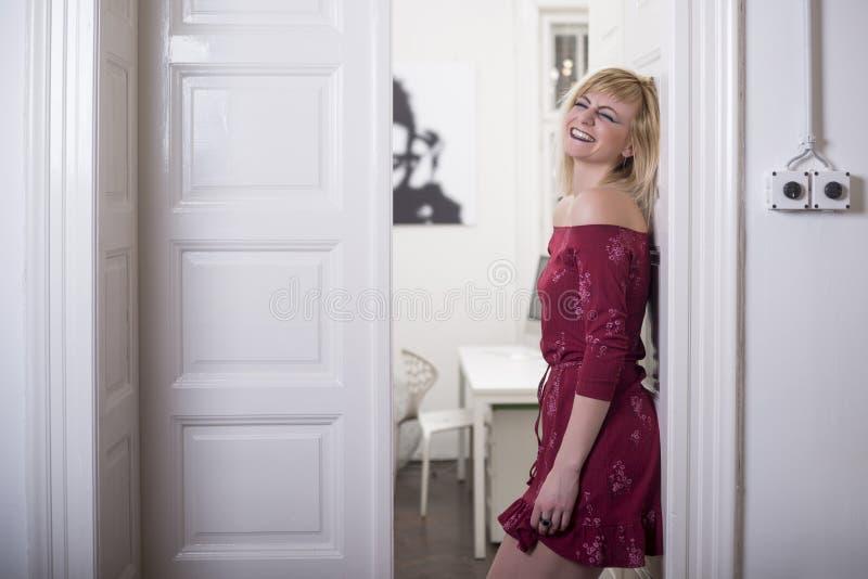 Härlig ung blond kvinna som bär rött le för klänning arkivbild