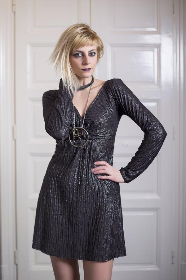 Härlig ung blond kvinna som framme bär den mörka klänningen av vit doornc royaltyfri fotografi