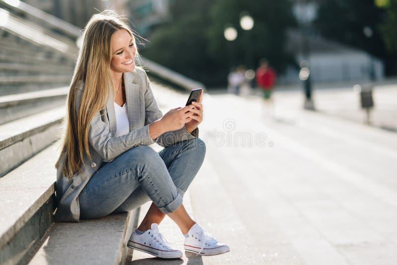 Härlig ung blond kvinna som ser hennes smartphone och smili royaltyfri bild