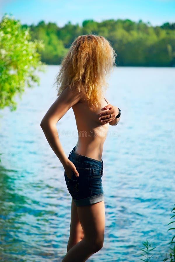 Härlig ung blond kvinna som står topless i floden royaltyfri bild