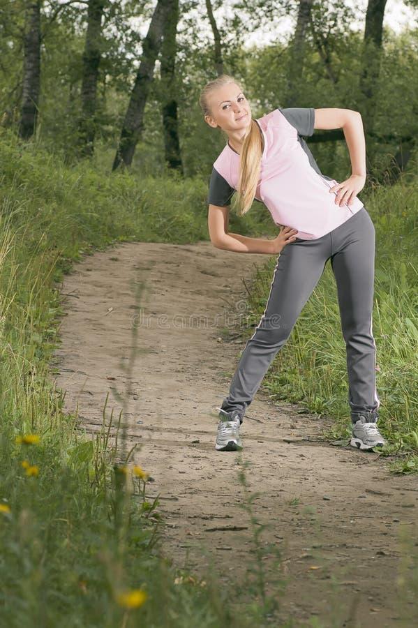 Härlig ung blond kvinna som värmer upp på en skogvandringsled arkivfoton