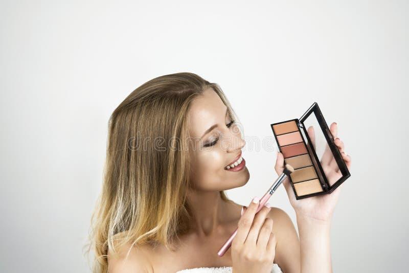 Härlig ung blond kvinnainnehavborste och isolerad vit bakgrund för eyeshagow palett royaltyfri bild