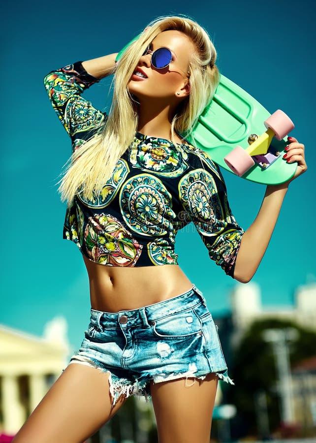 Härlig ung blond modellflicka i sommarhipsterkläder med skateboarden arkivfoton