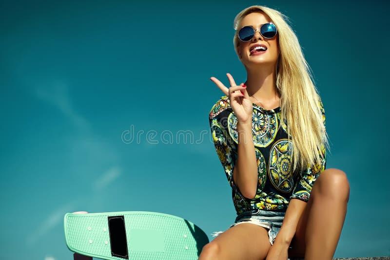 Härlig ung blond modellflicka i sommarhipsterkläder med skateboarden royaltyfri foto
