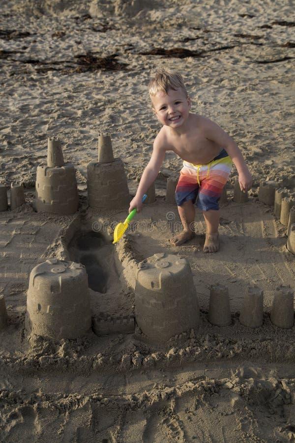 Härlig ung blond pojke som spelar på stranden i en sandslott arkivfoton