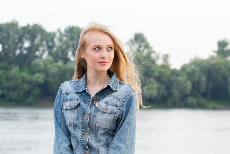 Härlig ung blond studentflicka i blått grov bomullstvillomslag som bort ler och ser på naturbakgrund arkivfoton
