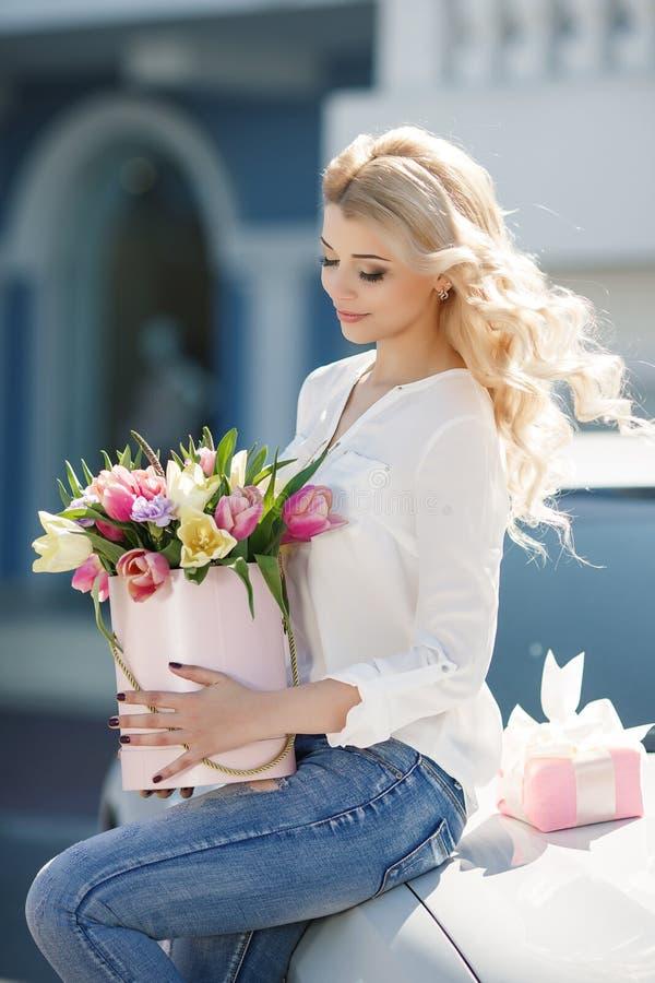 Härlig ung blondin med krabbt hår utomhus med en stor bukett av blommor på en ljus gata i staden arkivfoton