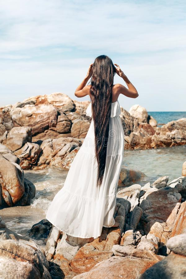 Härlig ung bohostilkvinna i det vita klänninganseendet på ston arkivbild