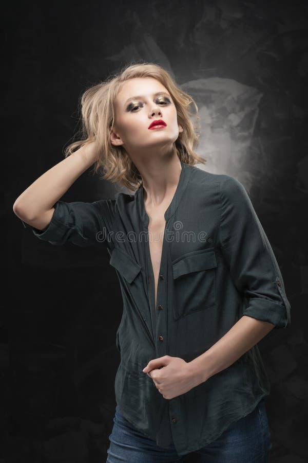 H?rlig ung braless slank blond flicka med ov?rdat h?r och aggressiv makeup och att b?ra en kn?ppt upp skjorta och jeans arkivbild