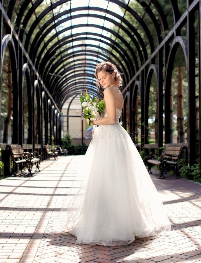 Härlig ung brud med att gifta sig buketten utomhus arkivfoto