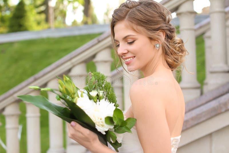 Härlig ung brud med att gifta sig buketten utomhus royaltyfria bilder