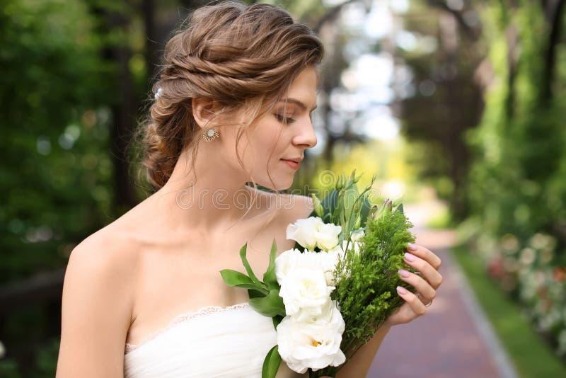 Härlig ung brud med att gifta sig buketten utomhus royaltyfri bild