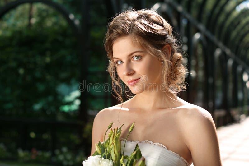 Härlig ung brud med att gifta sig buketten utomhus royaltyfri fotografi
