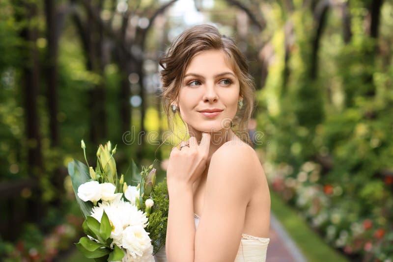 Härlig ung brud med att gifta sig buketten utomhus arkivbilder
