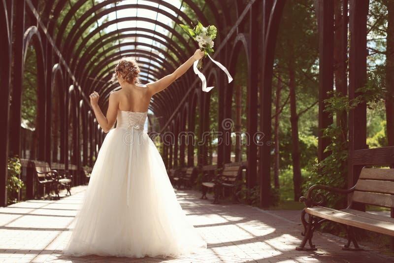 Härlig ung brud med att gifta sig buketten utomhus arkivbild