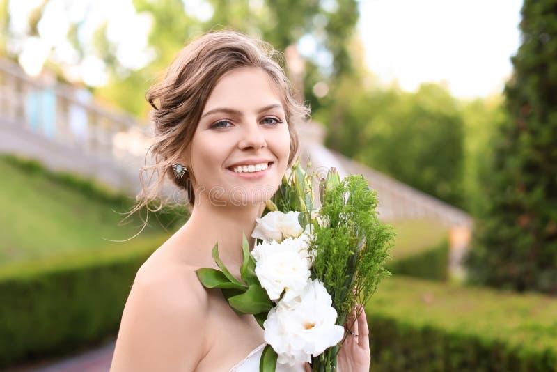 Härlig ung brud med att gifta sig buketten utomhus arkivfoton