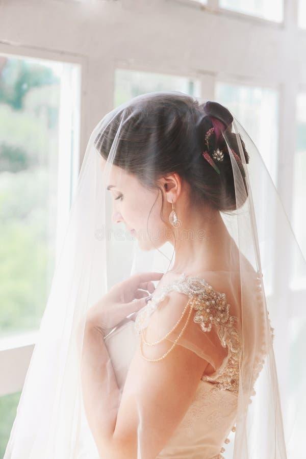 Härlig ung brud med bröllopmakeup och frisyr i sovrum Den härliga brudståenden med skyler över hennes framsida Closeupportr fotografering för bildbyråer
