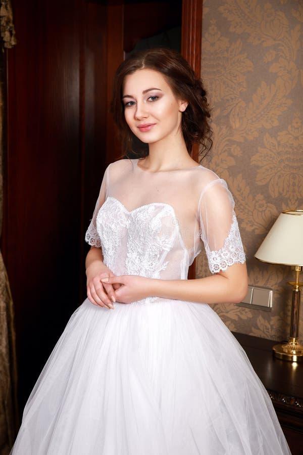 Härlig ung brud med brunetthår i ett sovrum Klassisk vit bröllopsklänning tät stående upp royaltyfria bilder