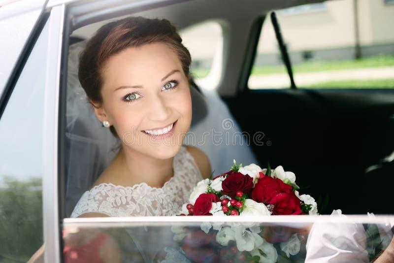 Härlig ung brud med buketten i bröllopbil royaltyfri bild