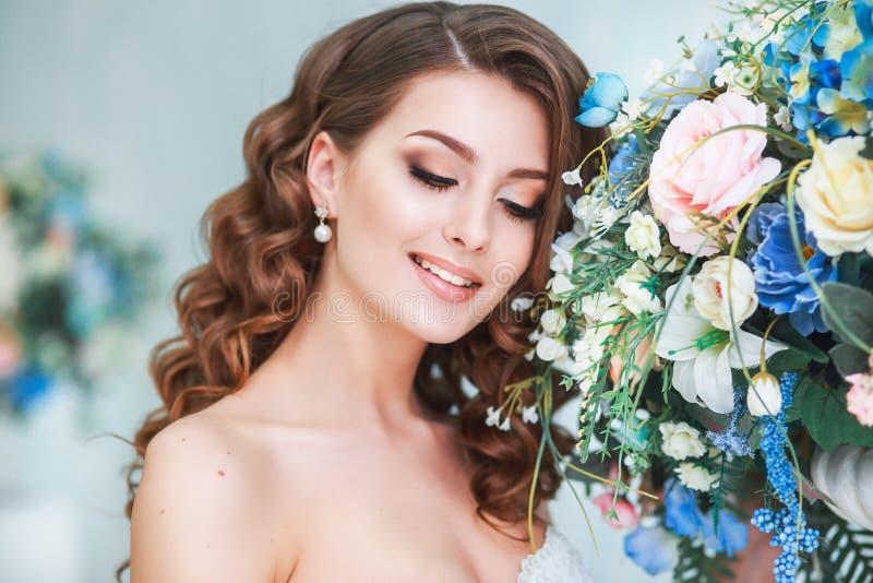 Härlig ung brud med den bröllopmakeup och frisyren inomhus Closeupstående av den unga ursnygga bruden i studio royaltyfri fotografi