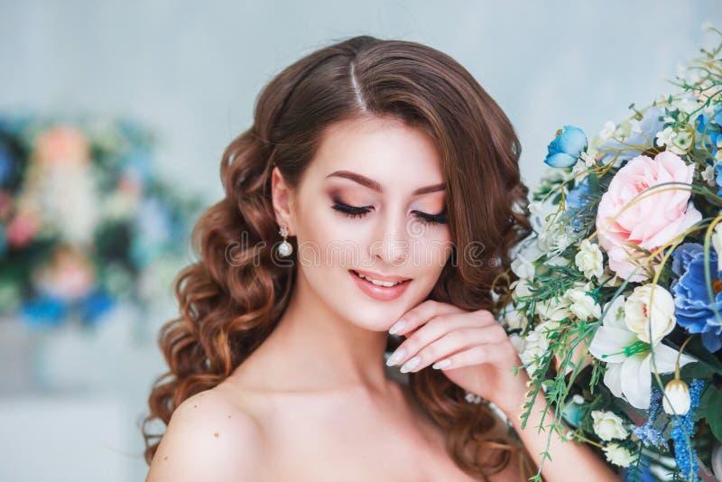 Härlig ung brud med den bröllopmakeup och frisyren inomhus Closeupstående av den unga ursnygga bruden i studio arkivfoto