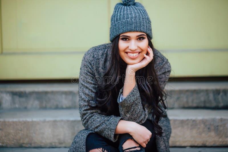 Härlig ung brunett med den svarta hatten som poserar och sitter på en bänk i stadsgatorna royaltyfria bilder